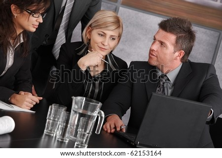 Businessman showing data on laptop computer during business meeting. Businesswomen looking at screen, thinking.? - stock photo
