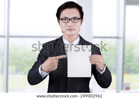 Businessman showing empty placard in the office - stock photo