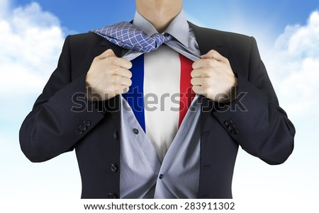 businessman showing France flag underneath his shirt over blue sky - stock photo