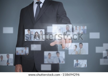 Businessman showing futuristic interface of coworkers posing - stock photo