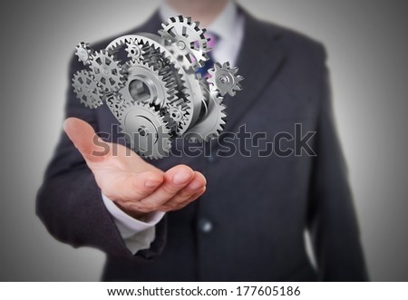 Businessman showing gears - stock photo