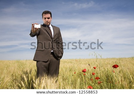 businessman showing his business card in a spring field - stock photo