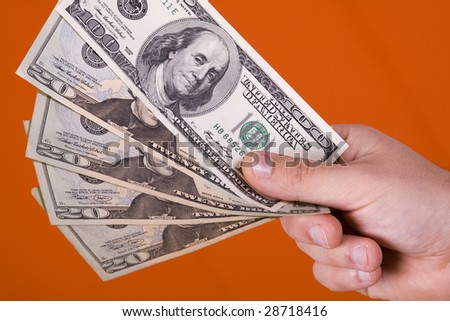 businessman showing his money with a orange background (selective focus) - stock photo