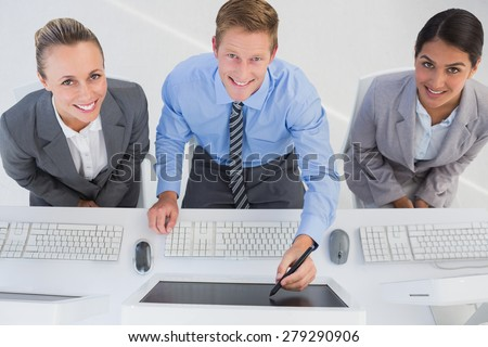 Businessman showing his screen to the team in office - stock photo