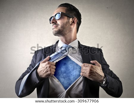 Businessman showing his super powers - stock photo