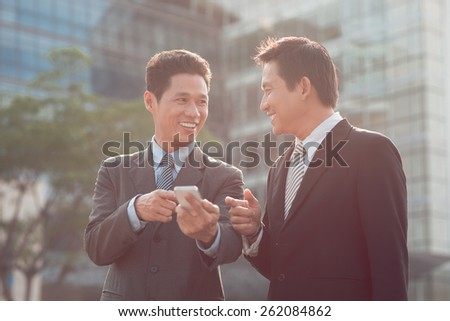 Businessman showing message on the phone to his colleague