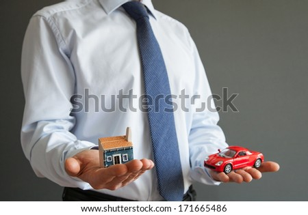 Businessman showing models of a house and a car - closeup shot - stock photo