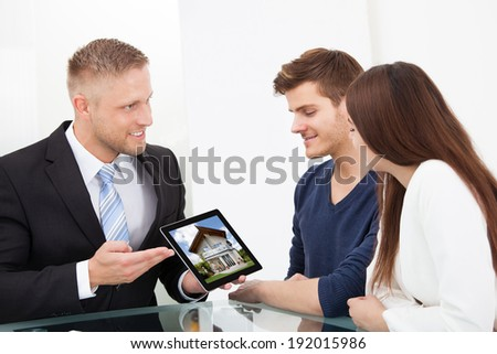 Businessman showing photo of a new home to couple on tablet at office desk - stock photo