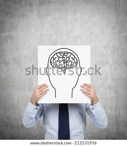 Businessman showing poster of sketched human brain. Brainstorming and inspiration concept. - stock photo