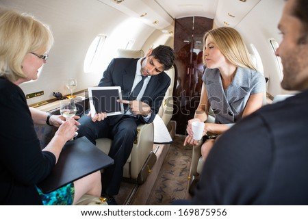 Businessman showing project on digital tablet to partners in private plane - stock photo