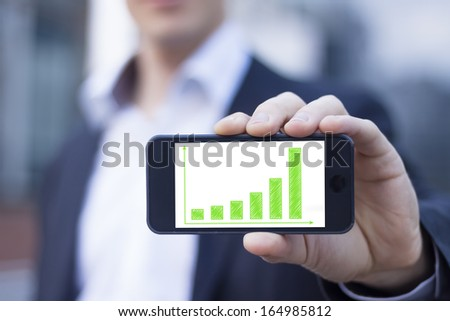 Businessman showing smartphone screen with sustainable development results on green bar chart - stock photo