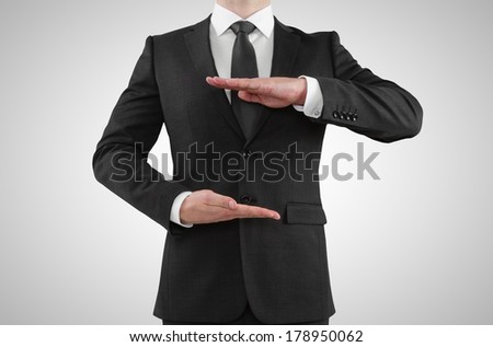 Businessman showing something on a gray background