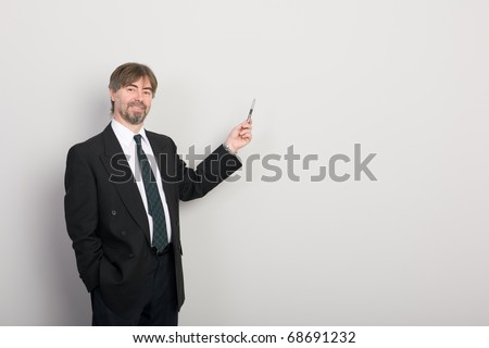 Businessman showing something on a gray background. - stock photo