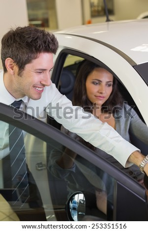 Businessman showing something to his customer at new car showroom - stock photo