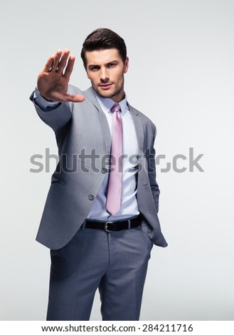 Businessman showing stop gesture over gray background. Looking at camera - stock photo