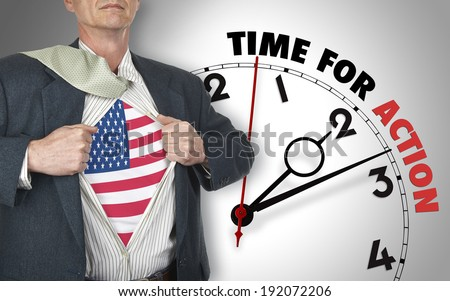 Businessman showing superhero suit with flag from USA underneath his shirt standing against clock with time for action - path for the shirt - stock photo
