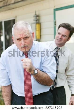 Businessman showing symptoms of flu or other illness such as ebola.  Worried friend and business colleague in background.   - stock photo