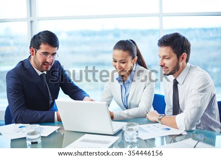 Businessman showing the presentation on computer to his colleagues - stock photo