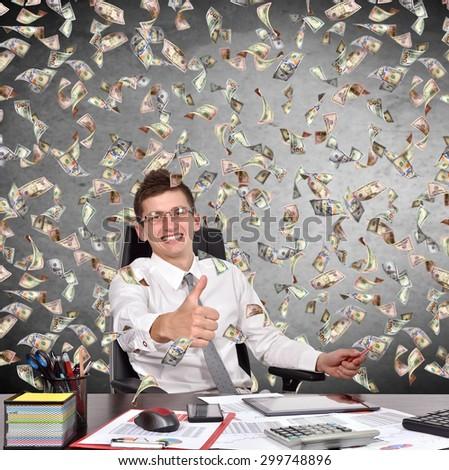 businessman showing thumb up and falling dollar bills - stock photo