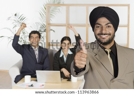 Businessman showing thumbs up sign - stock photo