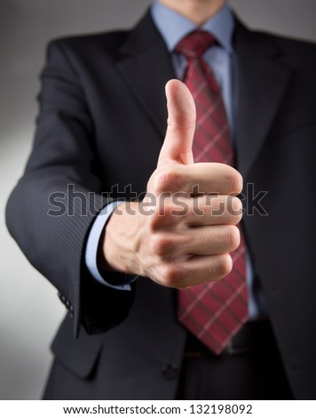 Businessman showing thumbs up sign. Neutral background - stock photo