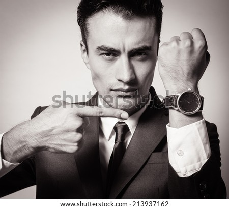 Businessman showing time on his wrist watch. - stock photo