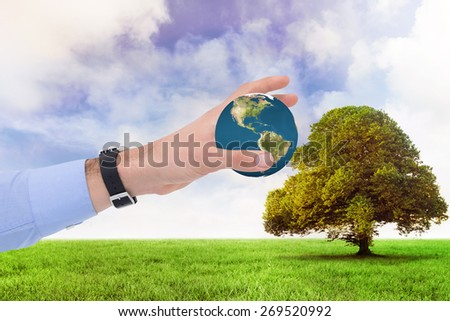 Businessman showing with his hand against tree in green field - stock photo