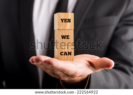 Businessman Showing Yes We Can Texts in Piled Small Wooden Blocks on Palm. - stock photo