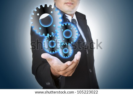 Businessman shows gear to success - stock photo