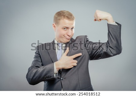 Businessman shows his muscles - stock photo