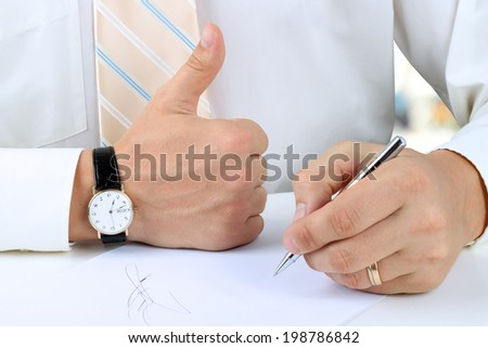 Businessman  signing a document  by pen and showing OK sign with his thumb up.  - stock photo