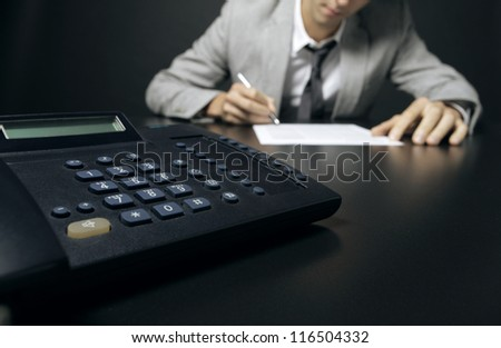 businessman signing a document, his phone in the foreground - stock photo