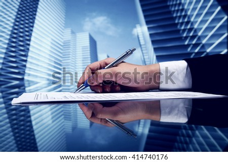 Businessman signing a document on futuristic skyscrapers background - stock photo