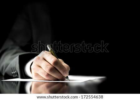 Businessman signing a document, taking notes, completing a questionnaire or writing correspondence, close up view of his hand and the paper