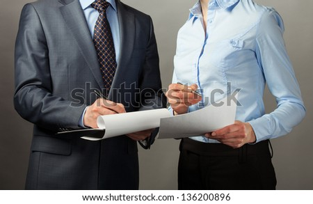 Businessman signing contract/document, grey background - stock photo