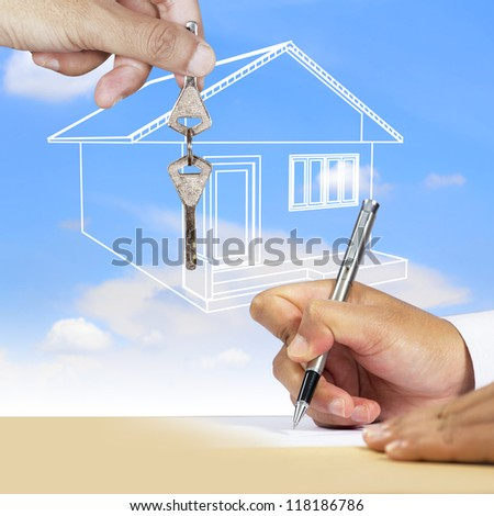 Businessman signing document with key and house as a background
