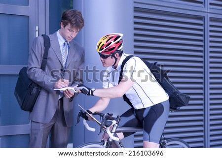 Businessman signing for bicycle courier - stock photo