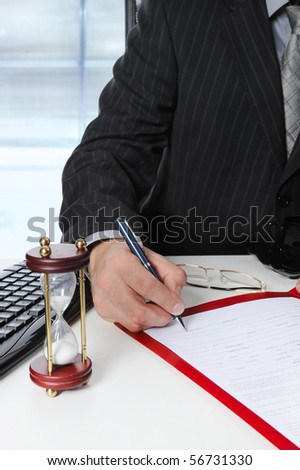 Businessman signs a document at the office at the workplace - stock photo