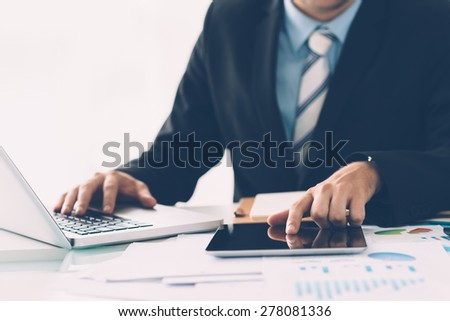 Businessman simultaneously using laptop and digital tablet: technology in business concept - stock photo