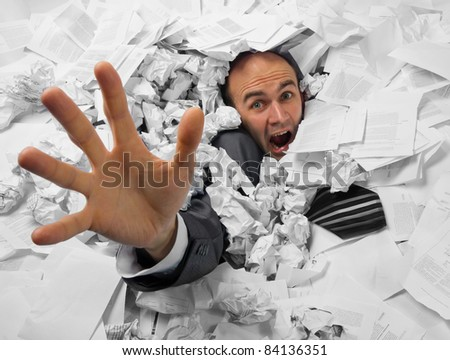 Businessman sinking in heap of documents and asking for help - stock photo