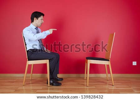 Businessman sited next to a red wall pointing to a empty chair