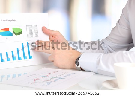 Businessman sitting and showing something on a  graphic by pen . Presentation. - stock photo
