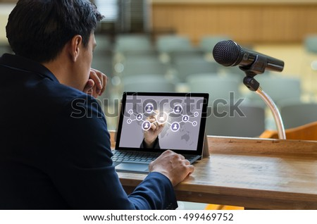Businessman sitting and using computer laptop showing the Social media symbol over Microphone on the speech podium over the Abstract blurred photo of conference hall, Business meeting concept