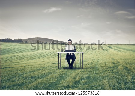 Businessman sitting at a desk on a large field using a laptop - stock photo