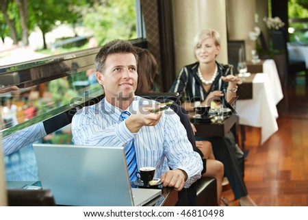 Businessman sitting at coffe table in cafe, paying with credit card, smiling. - stock photo