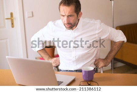 businessman sitting at desk and looking stressed at his laptop - stock photo