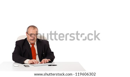 businessman sitting at desk and typing on keyboard with copy scape, isolated on white