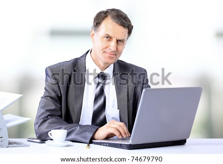 Businessman sitting at desk and working with laptop computer. - stock photo