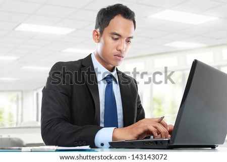 businessman sitting at desk in bright office working on laptop