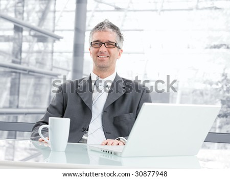Businessman sitting at desk in corporate office, working with laptop computer. Looking at camera, smiling.